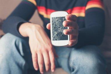 Man holding broken smart phone
