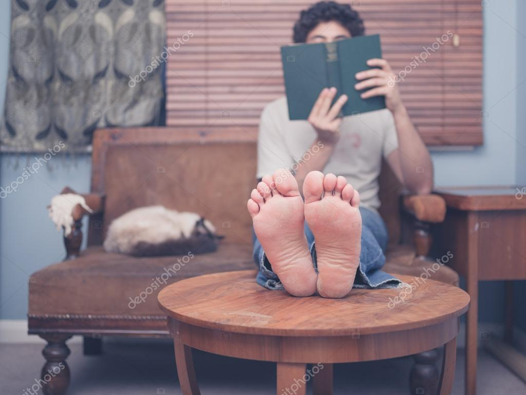 Barefoot man reading at home stock photo lofilolo 71684055 a barefoot young man is resting his legs on a coffee table at home while reading there is a cat on the sofa next to him photo by lofilolo malvernweather Images