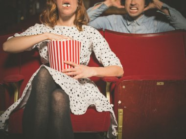 Woman annoying man in cinema by eating popcorn