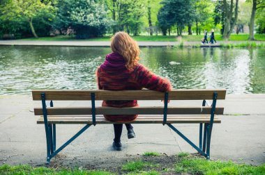 Woman sittng on bench by a pond in the park