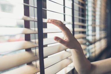 Female hand touching venetian blinds