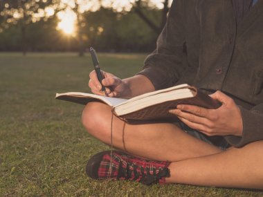 Woman writing in notebook at sunset