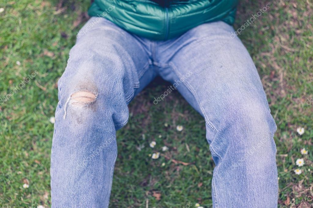 Moderní mladý muž s otvorem roztrhané džínsy na kolena je sedět na trávě —  Fotografie od ... 65ee5e8522