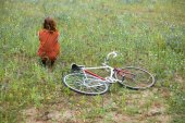 Woman sitting in meadow with bicycle