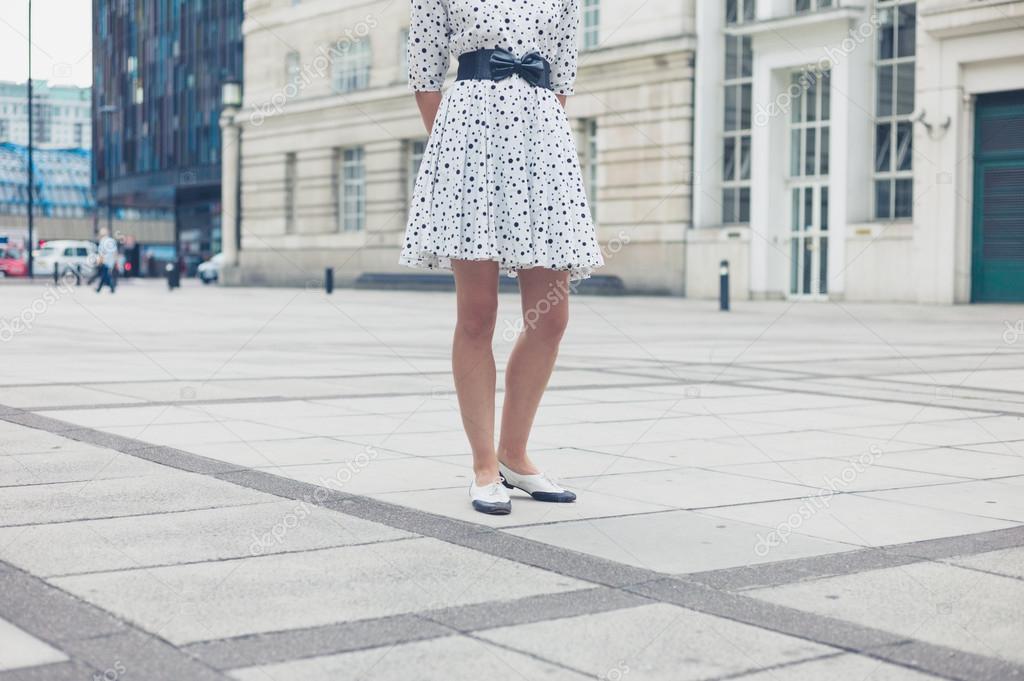 a56487615a Una mujer joven vistiendo un vestido blanco con puntos negros está de pie  en una plaza de la ciudad — Foto de ...