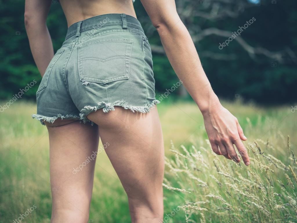 Woman touching grass in forest
