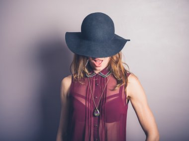 Happy young woman in hat and see through shirt