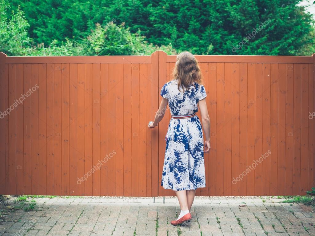 Young woman opening  orange gate