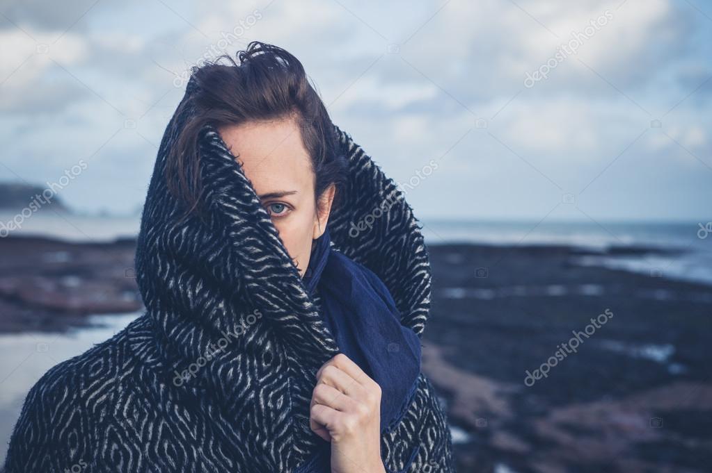Woman with hood on beach