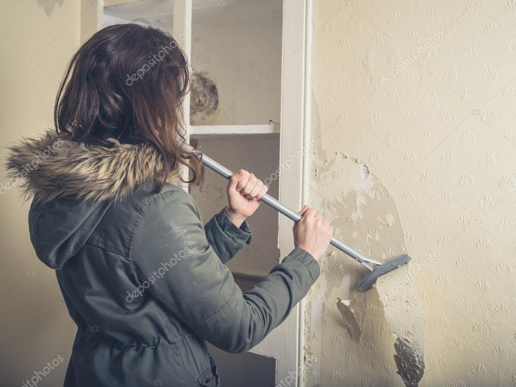 A Young Woman Wearing Warm Winter Coat Is Renovating House And Stripping Off The Wallpaper Photo By Lofilolo