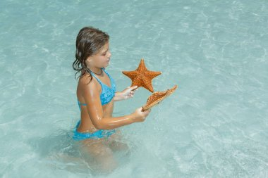 Joyful little girl sitting in azure crystal clear ocean and looking at starfish
