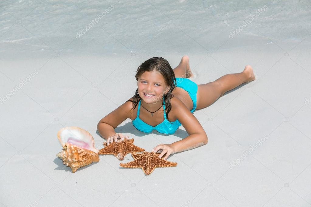 Joyful happy little girl lying on  white sand beach and playing with starfish and seashell