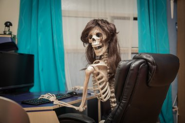 Smiling, crazy skeleton in a wig sitting in room on black leather chair behind the desktop
