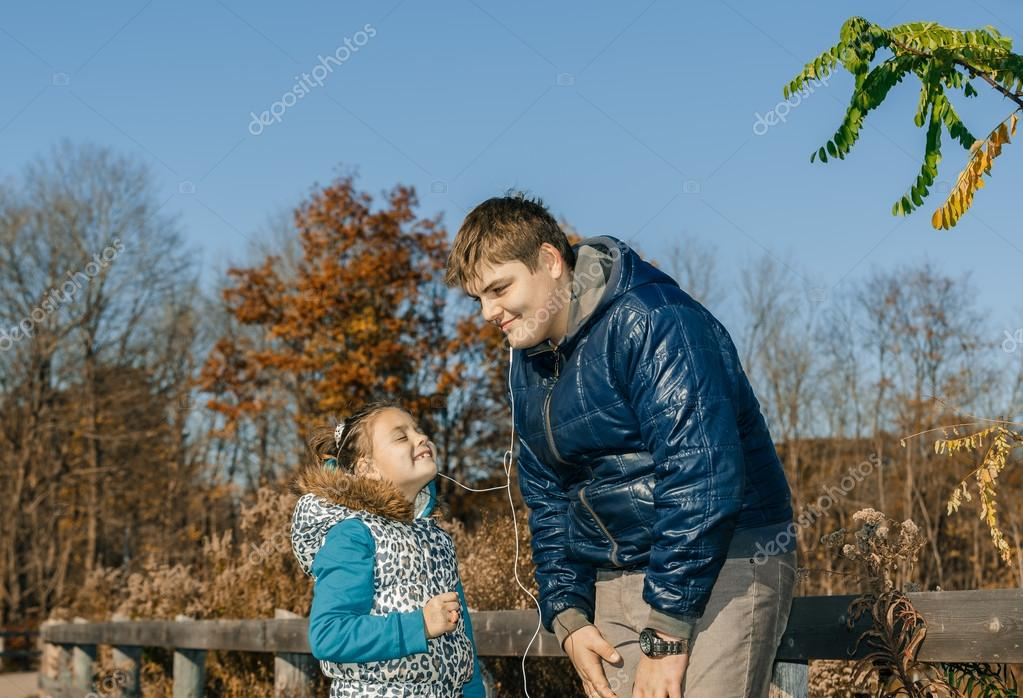 brother sharing the headphones with little joyful sister and listening funny music in autumn park on sunny beautiful day