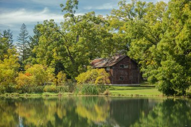Amazing view of an  old vintage wooden abandoned cabin, standing in woods reflected in lake calm water on sunny warm autumn day