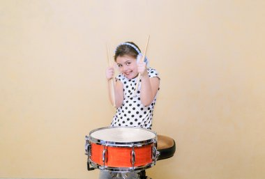 Joyful, charming fashionable little girl  in motion sitting behind the snare drum and holding a sticks in her hands