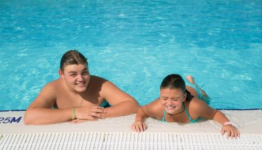 smiling children swimming and relaxing in water pool with natural ocean water on sunny summer day