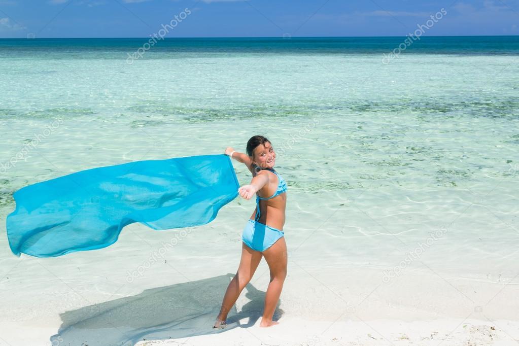 pretty stylish beautiful little girl walking on the tropical beach
