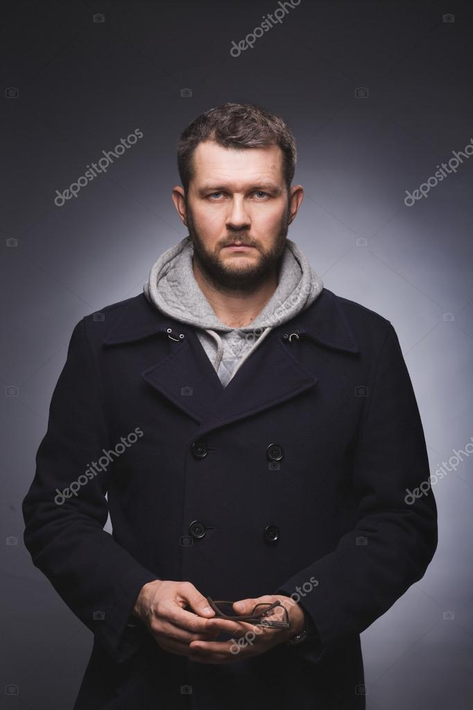 portrait of serious man in knitted jacket and blue pea coat over