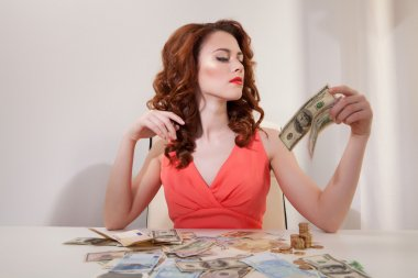 beautiful business woman in  pink dress on  table are the banknotes of t Euro and USD
