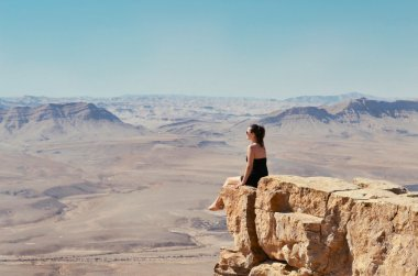 Girl on a cliff looking at desert landscape