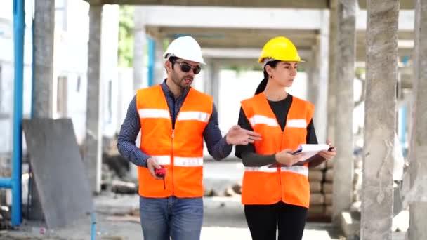 Schöne Ingenieurin mit einem männlichen Vorarbeiter mit Schutzhelm Über Arbeitsprobleme sprechen, Bauprojekte gemeinsam treffen.