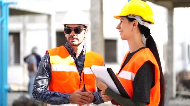 Schöne Ingenieurin mit einem männlichen Vorarbeiter mit Schutzhelm, sprechen gemeinsam über Arbeitsprobleme, treffen sich zu gemeinsamen Bauprojekten.