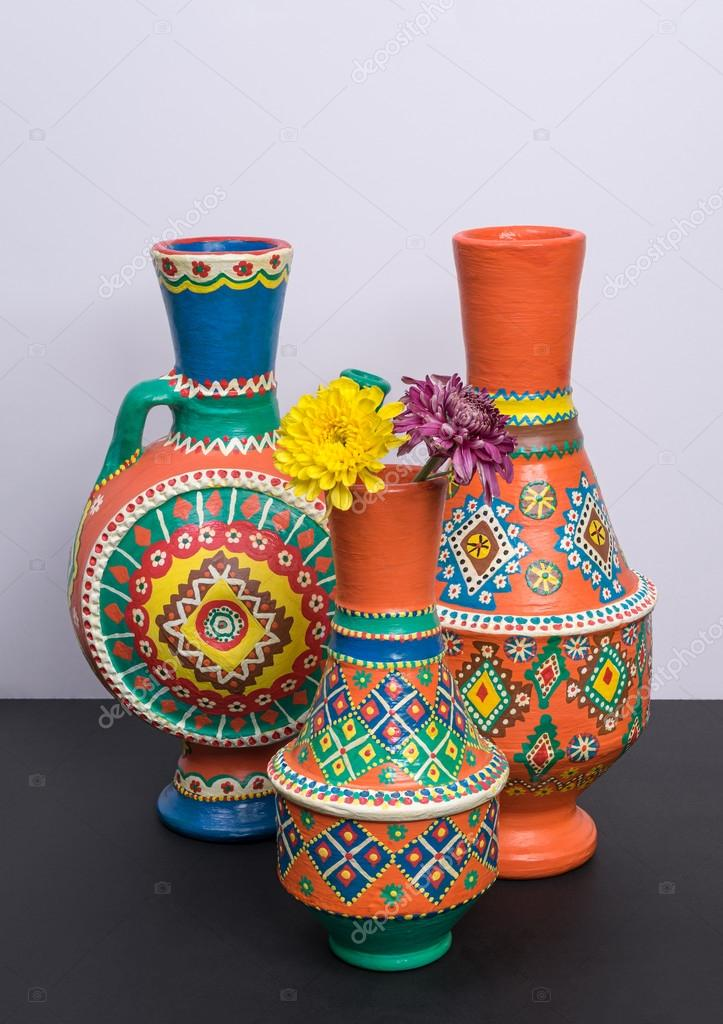 Three Ornate Pottery Vases With Two Yellow And Violet Flower Stock