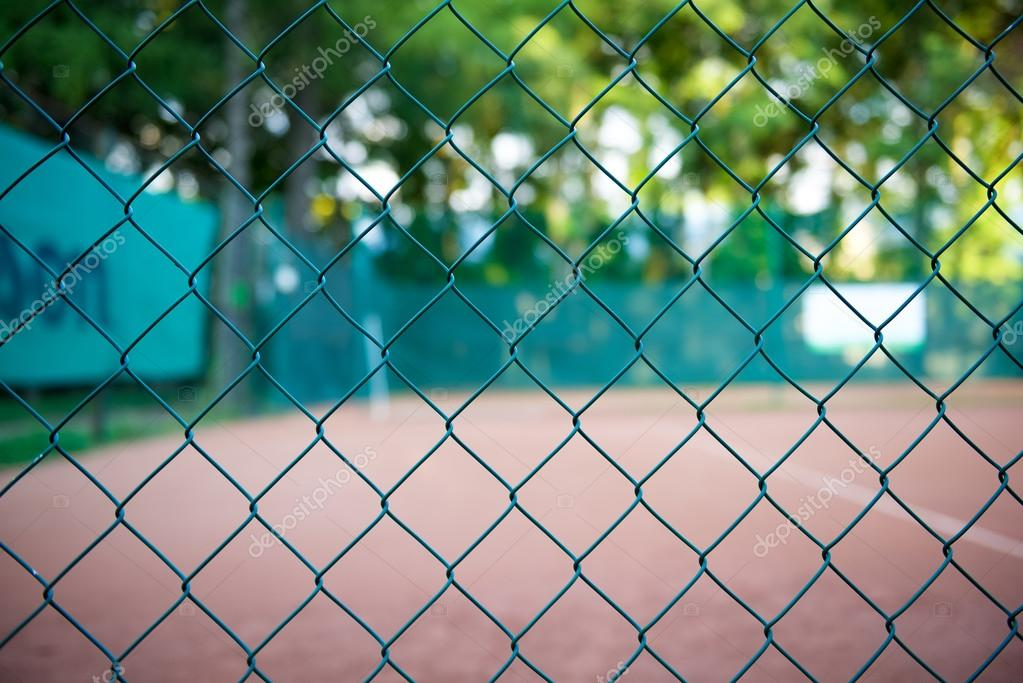 Valla de alambre con cancha de tenis en el fondo Foto de stock