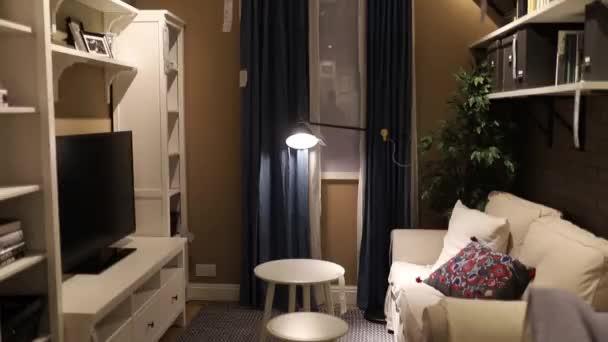Gemütliches kleines Wohnzimmer voller weißer Möbel und brauner Wände