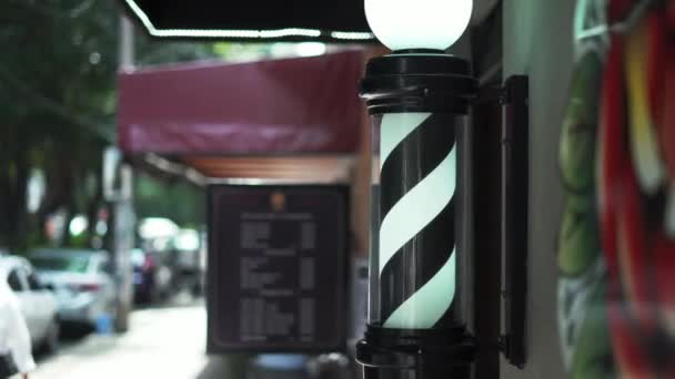 Traditional Black and White Barber Pole Light Outside a Barbershop
