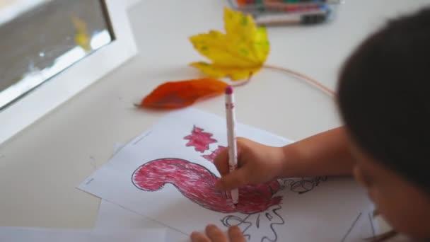 Kislány színezi a mókus képet egy papírlapon egy piros marker