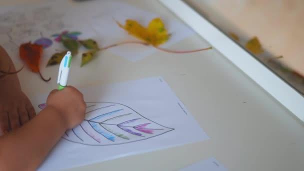 A kislány egy nagy levélképet fest egy papírlapon egy tollal.