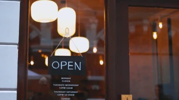 Černá Otevřená cedule visící na skleněných dveřích japonského saké baru