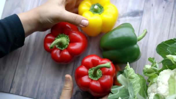 Žena ruce dávat barevné papriky dohromady na dřevěném stole