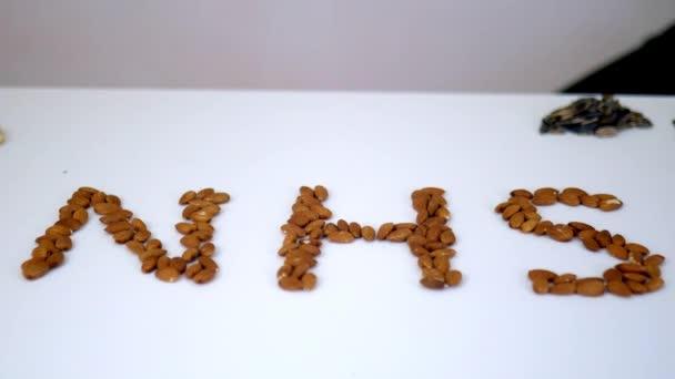 NHS-Buchstaben mit Mandeln über einem weißen Tisch