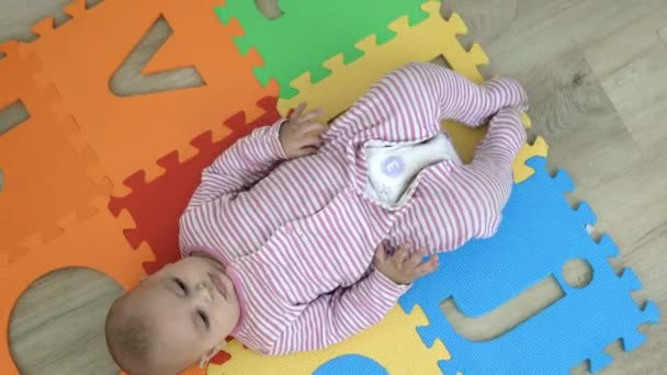 Adorable baby lying on a colorful foam mat