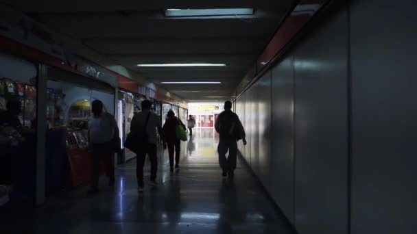 People walking in a dark corridor from the Mexico City subway