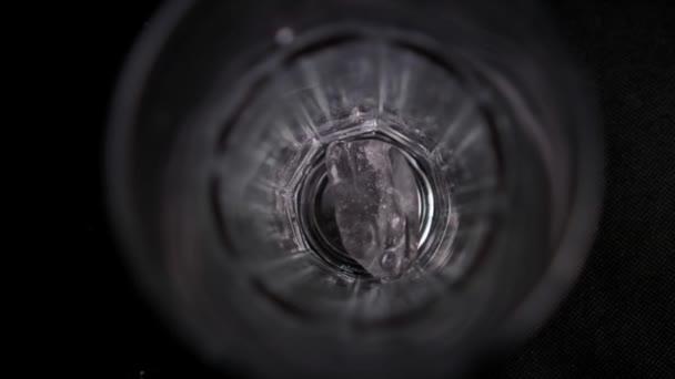 Hand lässt Eiswürfel langsam in ein Glas fallen