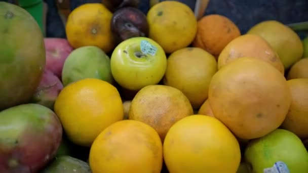 Close-up of colorful fruit stand with mangoes, oranges, and more