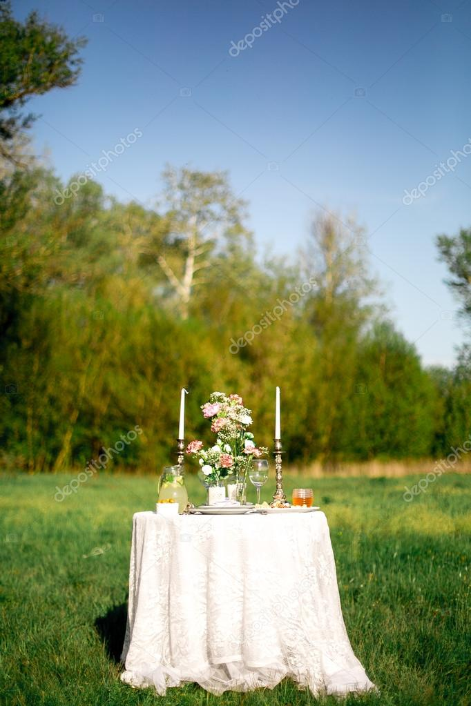 beautifully laid a festive table for two in the garden with flowers and candles