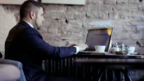 Uomo daffari lavora con il computer portatile nella caffetteria