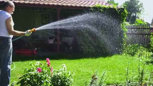 Älterer Mann Bewässerung des Rasens
