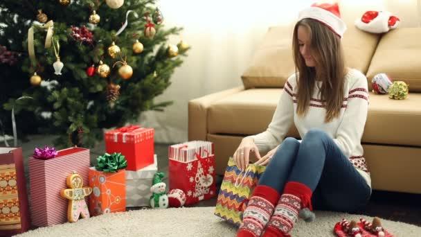 Krásná mladá dívka zabalený vánoční dárek