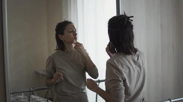 Žena dělá vlastní masáž obličeje doma