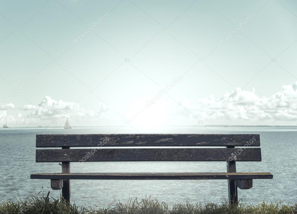 Wooden bench in front of the sea.