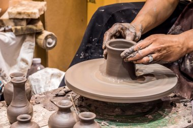Hands working on pottery.