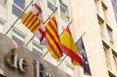 Vlajky vlající na vnější straně budovy, katalánské, španělské a barcelonské městské vlajky. Tři příznaky.