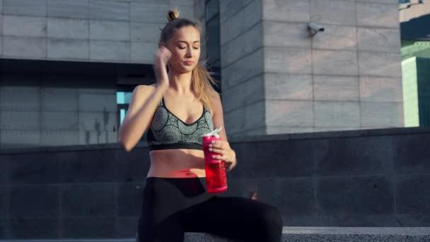 Unavená žena pít vodu červená láhev po ranním cvičení