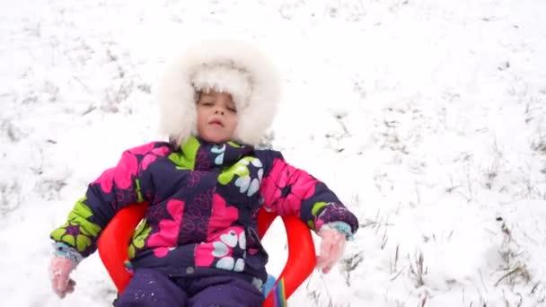 Kleines Mädchen im Winter in leuchtend warmer Kleidung fährt auf einem blauen Plastikschlitten